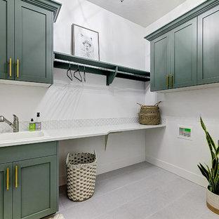 Inspiration för en stor lantlig vita l-formad vitt tvättstuga enbart för tvätt, med en nedsänkt diskho, skåp i shakerstil, gröna skåp, bänkskiva i kvarts, vita väggar, klinkergolv i porslin, en tvättmaskin och torktumlare bredvid varandra och grått golv