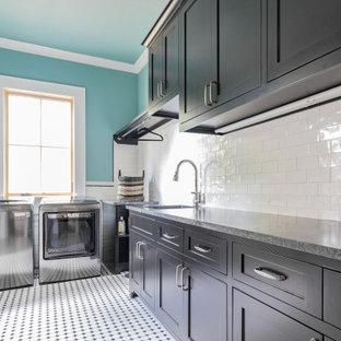 Idéer för stora lantliga l-formade svart tvättstugor enbart för tvätt, med en undermonterad diskho, skåp i shakerstil, svarta skåp, granitbänkskiva, blå väggar, klinkergolv i keramik, en tvättmaskin och torktumlare bredvid varandra och flerfärgat golv