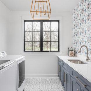 Ispirazione per una sala lavanderia country con lavello sottopiano, ante in stile shaker, ante grigie, pareti multicolore, lavatrice e asciugatrice affiancate, pavimento multicolore e top bianco
