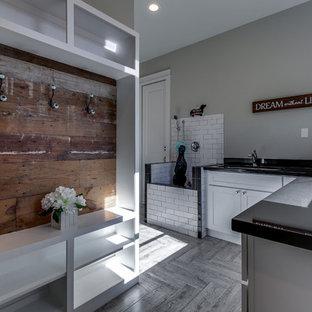Inspiration för stora lantliga l-formade grovkök, med en allbänk, skåp i shakerstil, vita skåp, granitbänkskiva, grå väggar, klinkergolv i porslin, en tvättmaskin och torktumlare bredvid varandra och grått golv