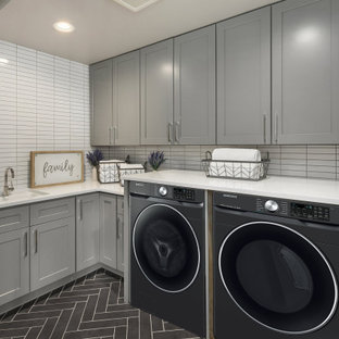 Example of a transitional l-shaped gray floor dedicated laundry room design in Chicago with an undermount sink, shaker cabinets, gray cabinets, white backsplash, white walls, a side-by-side washer/dryer and white countertops