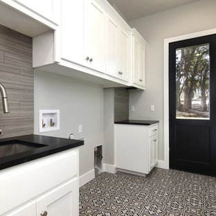 Medium sized country galley separated utility room in Austin with a submerged sink, shaker cabinets, white cabinets, composite countertops, grey walls, porcelain flooring, a side by side washer and dryer, grey floors and black worktops.