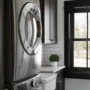 Immagine di una piccola sala lavanderia tradizionale con lavello stile country, ante in stile shaker, ante nere, top in superficie solida, pareti bianche, lavatrice e asciugatrice a colonna, pavimento multicolore e top bianco