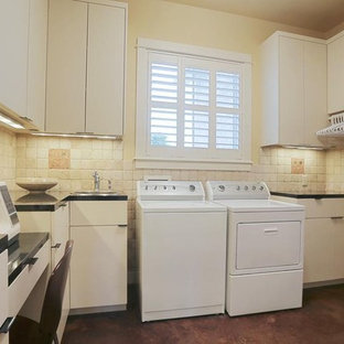 Design ideas for a medium sized rural l-shaped utility room in Houston with a built-in sink, flat-panel cabinets, white cabinets, granite worktops, beige walls, concrete flooring, a side by side washer and dryer, brown floors and black worktops.