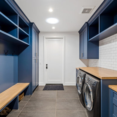 Inspiration for a huge cottage galley porcelain tile and gray floor utility room remodel in Los Angeles with an undermount sink, shaker cabinets, blue cabinets, wood countertops, white backsplash, ceramic backsplash, white walls, a side-by-side washer/dryer and beige countertops