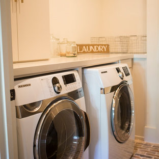 This is an example of a large rural single-wall separated utility room in Atlanta with flat-panel cabinets, white cabinets, composite countertops, white walls, brick flooring and a side by side washer and dryer.
