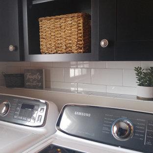 Immagine di una lavanderia multiuso country di medie dimensioni con lavatoio, ante in stile shaker, ante nere, top in legno, pareti beige, pavimento in cemento, lavatrice e asciugatrice affiancate, pavimento multicolore e top marrone