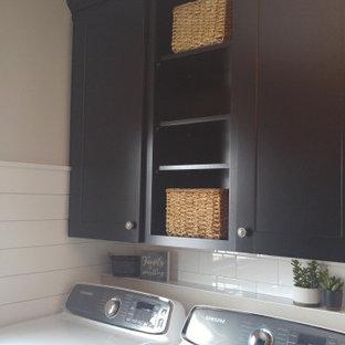 Esempio di una lavanderia multiuso di medie dimensioni con ante in stile shaker, ante nere, top in legno, pareti beige, pavimento in cemento, lavatrice e asciugatrice affiancate, pavimento multicolore e top marrone
