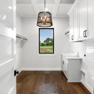 Inredning av en lantlig mellanstor vita vitt tvättstuga enbart för tvätt och med garderob, med en rustik diskho, luckor med infälld panel, vita skåp, marmorbänkskiva, vitt stänkskydd, stänkskydd i porslinskakel, vita väggar, mörkt trägolv och brunt golv