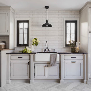 Inspiration for a large rural single-wall separated utility room in Denver with a belfast sink, recessed-panel cabinets, grey cabinets, soapstone worktops, white walls, porcelain flooring, a side by side washer and dryer, grey floors and black worktops.