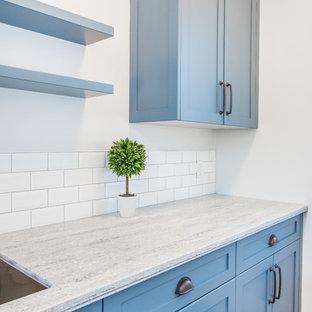 Esempio di una piccola lavanderia multiuso country con lavello sottopiano, ante in stile shaker, ante blu, top in superficie solida, pareti grigie, pavimento in gres porcellanato, lavatrice e asciugatrice affiancate, pavimento grigio e top grigio