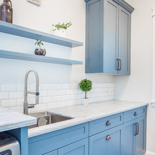 Design ideas for a small rural galley utility room in Vancouver with a submerged sink, shaker cabinets, blue cabinets, composite countertops, grey walls, porcelain flooring, a side by side washer and dryer, grey floors and grey worktops.