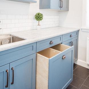 Idee per una piccola lavanderia multiuso country con lavello sottopiano, ante in stile shaker, ante blu, top in superficie solida, pareti grigie, pavimento in gres porcellanato, lavatrice e asciugatrice affiancate, pavimento grigio e top grigio