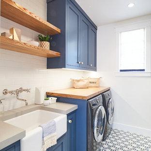 Maritim inredning av en grå linjär grått tvättstuga enbart för tvätt, med en rustik diskho, skåp i shakerstil, blå skåp, träbänkskiva, vita väggar, en tvättmaskin och torktumlare bredvid varandra och flerfärgat golv