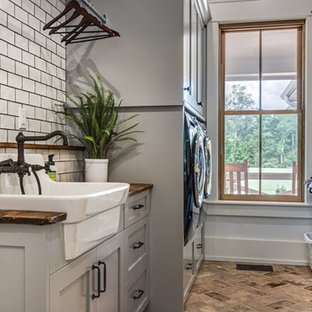 Mid-sized country galley brick floor and brown floor dedicated laundry room photo in Nashville with a farmhouse sink, shaker cabinets, gray cabinets, wood countertops, gray walls and brown countertops