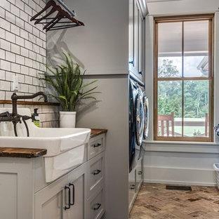 Esempio di una sala lavanderia country di medie dimensioni con lavello stile country, ante in stile shaker, ante grigie, top in legno, pareti grigie, pavimento in mattoni, lavatrice e asciugatrice affiancate, pavimento marrone e top marrone