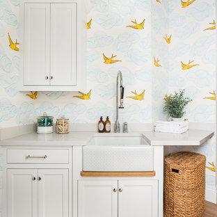 Inredning av en lantlig vita vitt tvättstuga, med en rustik diskho, luckor med infälld panel, vita skåp, flerfärgade väggar, mellanmörkt trägolv och brunt golv