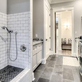 Exempel på en mellanstor lantlig parallell tvättstuga, med en undermonterad diskho, luckor med profilerade fronter, grå skåp, granitbänkskiva, grå väggar, en tvättmaskin och torktumlare bredvid varandra och grått golv