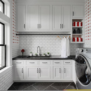 Large cottage l-shaped slate floor and black floor utility room photo in New York with shaker cabinets, white cabinets, white walls, a side-by-side washer/dryer, black countertops and an undermount sink