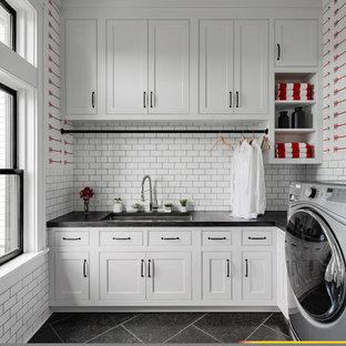 Immagine di una grande lavanderia multiuso country con ante in stile shaker, ante bianche, pareti bianche, pavimento in ardesia, lavatrice e asciugatrice affiancate, pavimento nero, top nero e lavello sottopiano
