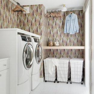 Lantlig inredning av en vita vitt tvättstuga enbart för tvätt, med skåp i shakerstil, vita skåp, flerfärgade väggar, en tvättmaskin och torktumlare bredvid varandra och vitt golv