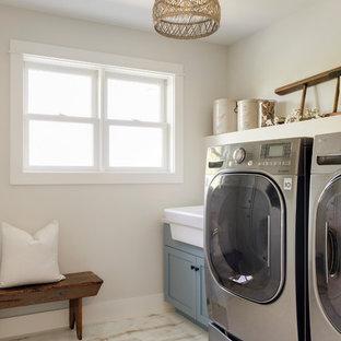 Immagine di una sala lavanderia moderna di medie dimensioni con lavello stile country, ante a filo, ante blu, pareti beige, pavimento in legno verniciato, lavatrice e asciugatrice affiancate e pavimento bianco