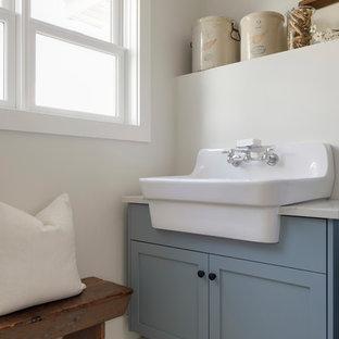 Idées déco pour une buanderie moderne dédiée et de taille moyenne avec un évier de ferme, un placard à porte affleurante, des portes de placard bleues, un mur beige, un sol en bois peint, des machines côte à côte et un sol blanc.