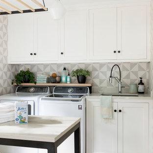 Foto på ett stort vintage vit grovkök, med en enkel diskho, luckor med infälld panel, vita skåp, bänkskiva i kvarts, klinkergolv i porslin, en tvättmaskin och torktumlare bredvid varandra och grått golv