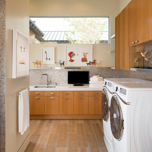Example of a large midcentury modern l-shaped porcelain floor dedicated laundry room design in Austin with an undermount sink, flat-panel cabinets, medium tone wood cabinets, quartzite countertops, beige walls and a side-by-side washer/dryer