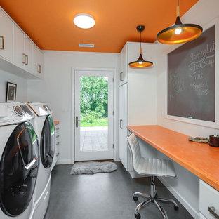 Foto på ett mellanstort industriellt orange parallellt grovkök, med en allbänk, släta luckor, vita skåp, laminatbänkskiva, orange väggar, betonggolv, en tvättmaskin och torktumlare bredvid varandra och grått golv