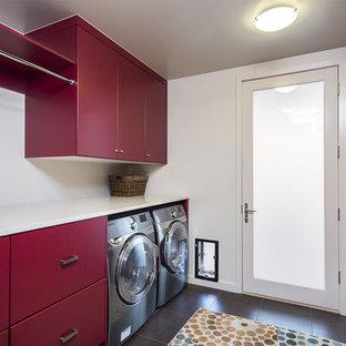Modern inredning av en mellanstor parallell tvättstuga enbart för tvätt, med släta luckor, röda skåp, vita väggar, en tvättmaskin och torktumlare bredvid varandra, bänkskiva i koppar, klinkergolv i porslin och svart golv