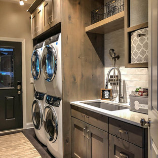 Inspiration for a large modern galley utility room in Chicago with a drop-in sink, distressed cabinets, quartz benchtops, beige walls, dark hardwood floors, a stacked washer and dryer, grey floor and white benchtop.