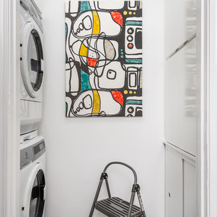 Laundry closet - small contemporary galley bamboo floor and gray floor laundry closet idea in Atlanta with flat-panel cabinets, white cabinets, white walls and a stacked washer/dryer