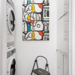 Modern inredning av en liten parallell liten tvättstuga, med släta luckor, vita skåp, bambugolv, grått golv, vita väggar och en tvättpelare