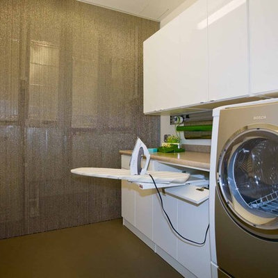 Inspiration for a mid-sized contemporary galley utility room remodel in Portland with flat-panel cabinets, white cabinets, a side-by-side washer/dryer and gray walls