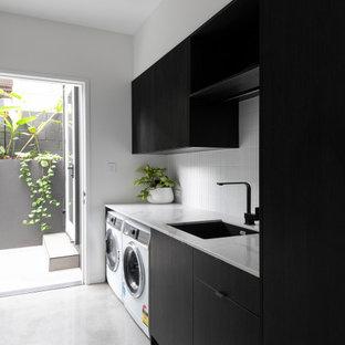Immagine di una lavanderia minimalista con lavello sottopiano, ante lisce, ante nere, pareti bianche, pavimento in cemento, lavatrice e asciugatrice affiancate, pavimento grigio e top bianco