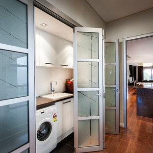 Réalisation d'une petite buanderie linéaire minimaliste avec un placard, un placard à porte affleurante, des portes de placard blanches, un plan de travail en quartz modifié, des machines côte à côte et un évier posé.