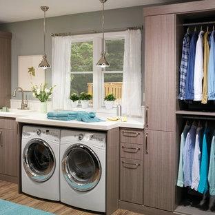 Inredning av en modern stor linjär tvättstuga enbart för tvätt, med en enkel diskho, släta luckor, en tvättmaskin och torktumlare bredvid varandra, bänkskiva i kvarts, grå väggar, mellanmörkt trägolv och grå skåp