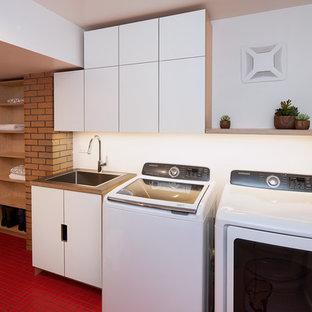 Idee per una lavanderia multiuso minimalista di medie dimensioni con lavatoio, ante lisce, ante in legno chiaro, top in laminato, pareti bianche, pavimento con piastrelle in ceramica, lavatrice e asciugatrice affiancate, pavimento rosso e top grigio