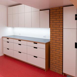 Foto på en mellanstor 60 tals grå tvättstuga, med en allbänk, släta luckor, skåp i ljust trä, laminatbänkskiva, vita väggar, klinkergolv i keramik, en tvättmaskin och torktumlare bredvid varandra och rött golv