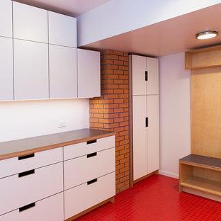 Inredning av ett 50 tals mellanstort grå grått grovkök, med en allbänk, släta luckor, skåp i ljust trä, laminatbänkskiva, vita väggar, klinkergolv i keramik, en tvättmaskin och torktumlare bredvid varandra och rött golv