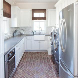 Bild på ett stort vintage u-format grovkök, med en rustik diskho, vita skåp, beige väggar, tegelgolv, en tvättmaskin och torktumlare bredvid varandra och skåp i shakerstil