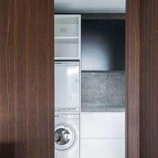 Foto på en mellanstor funkis l-formad tvättstuga, med skåp i mörkt trä, bänkskiva i koppar, grått stänkskydd, stänkskydd i cementkakel och klinkergolv i keramik