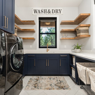 Inspiration for a country u-shaped dedicated laundry room in Seattle with an undermount sink, shaker cabinets, blue cabinets, grey walls, a side-by-side washer and dryer, beige floor and white benchtop.