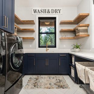 На фото: отдельная, п-образная прачечная в стиле кантри с врезной раковиной, фасадами в стиле шейкер, синими фасадами, серыми стенами, со стиральной и сушильной машиной рядом, бежевым полом и белой столешницей с