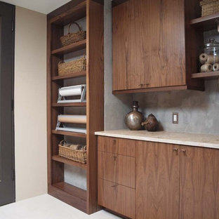 Mid-sized modern single-wall utility room in Chicago with flat-panel cabinets, limestone benchtops, dark wood cabinets and beige walls.