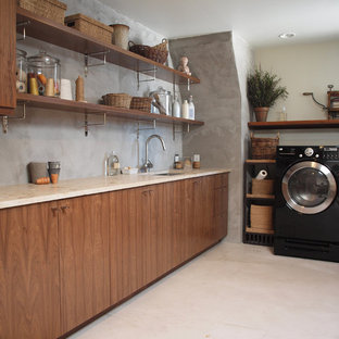 Photo of a medium sized contemporary l-shaped utility room in Chicago with flat-panel cabinets, a side by side washer and dryer, a submerged sink, medium wood cabinets, limestone worktops, grey walls, beige floors and beige worktops.