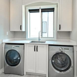 Immagine di una lavanderia multiuso minimalista di medie dimensioni con ante in stile shaker, ante bianche, lavatrice e asciugatrice affiancate, lavello sottopiano, top in quarzite, pareti beige e pavimento in travertino