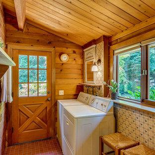 Foto di una lavanderia multiuso rustica di medie dimensioni con pavimento con piastrelle in ceramica, lavatrice e asciugatrice affiancate e pavimento rosso