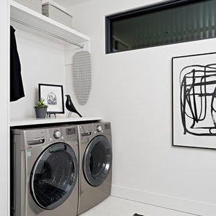 Cette image montre une buanderie parallèle minimaliste de taille moyenne avec un évier encastré, un placard à porte plane, un plan de travail en quartz modifié, un mur blanc, un sol en carrelage de porcelaine, des machines côte à côte, un sol blanc et un plan de travail blanc.
